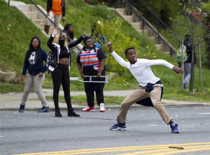 Demonstrators throw rocks at the police after the funeral of Freddie Gray on Monday, April 27, at New Shiloh Baptist Church in Baltimore. Gray died from spinal injuries about a week after he was arrested and transported in a Baltimore Police Department van.  NBC News